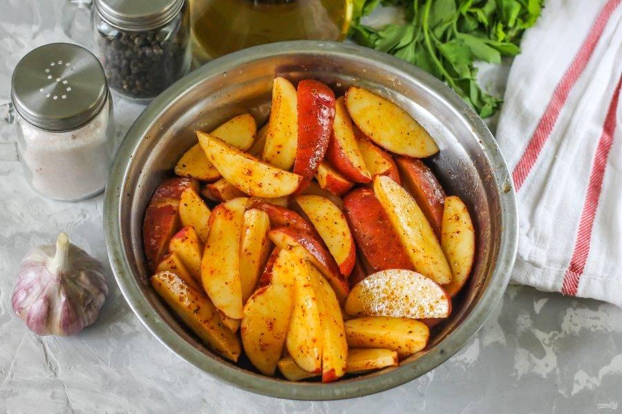 Аккуратно все перемешайте, чтобы паприка окрасила масло, а оно - ломтики картофеля.