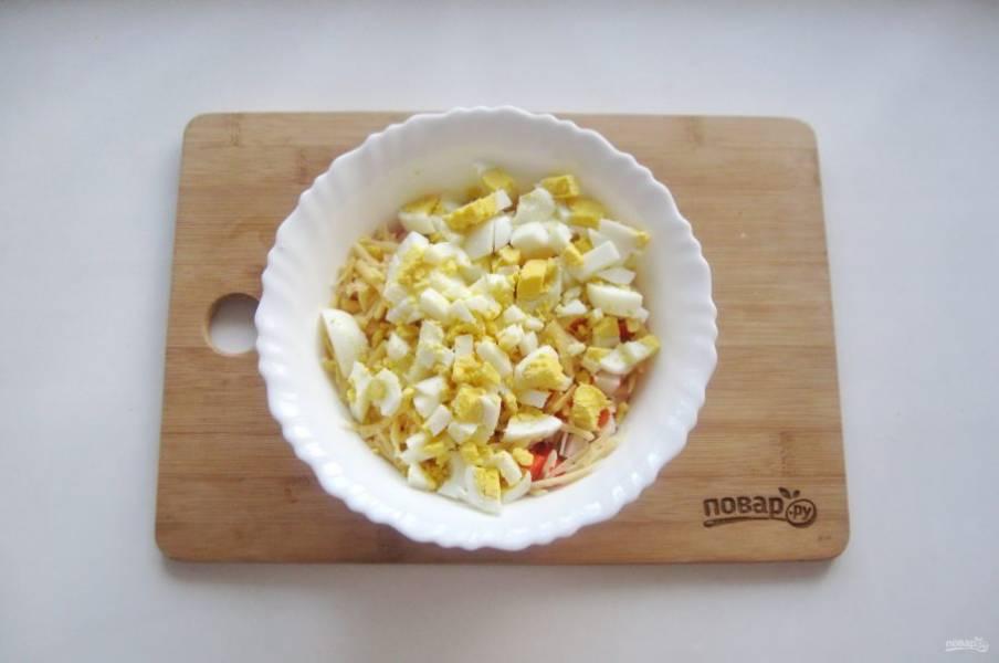 Яйца сварите вкрутую, охладите, очистите. Нарежьте кубиками и добавьте в салат.