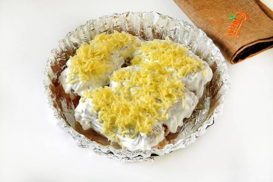 Смажьте сметаной и посыпьте оставшимся сыром. Запекайте при 180 градусах около 30 минут.