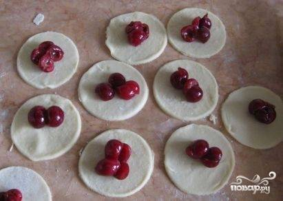 На середину каждого кружочка выкладываем ягоды. Если вишня кислая даже после настаивания с сахаром - можно насыпать немножко сахара.