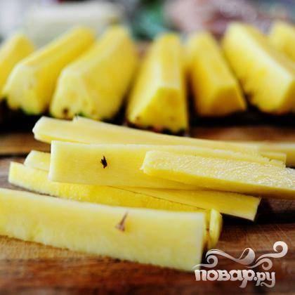 Нарежьте ананас на длинные ломтики.