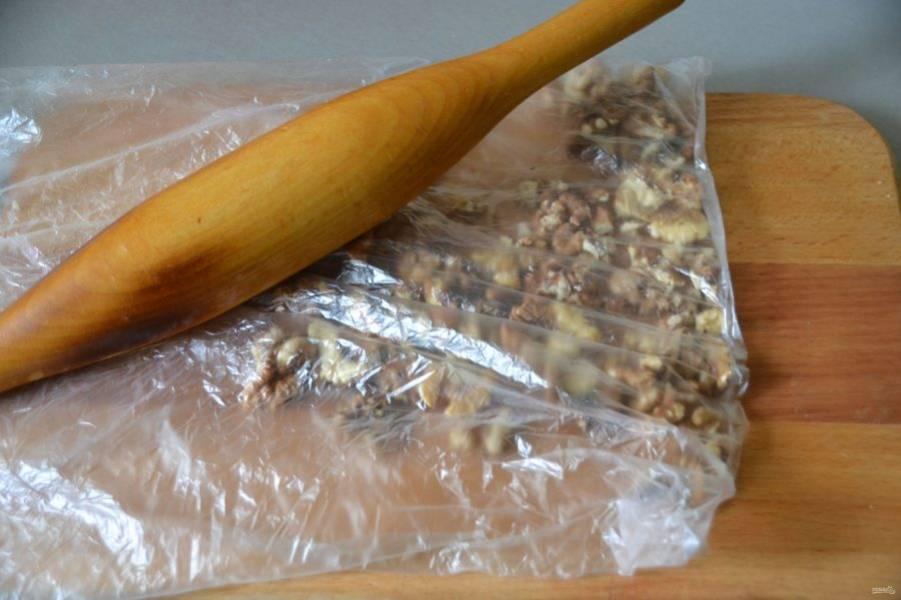 Остывшие орехи сложите в пакет и измельчите с помощью скалки, не слишком мелко, чтобы оставались небольшие кусочки.