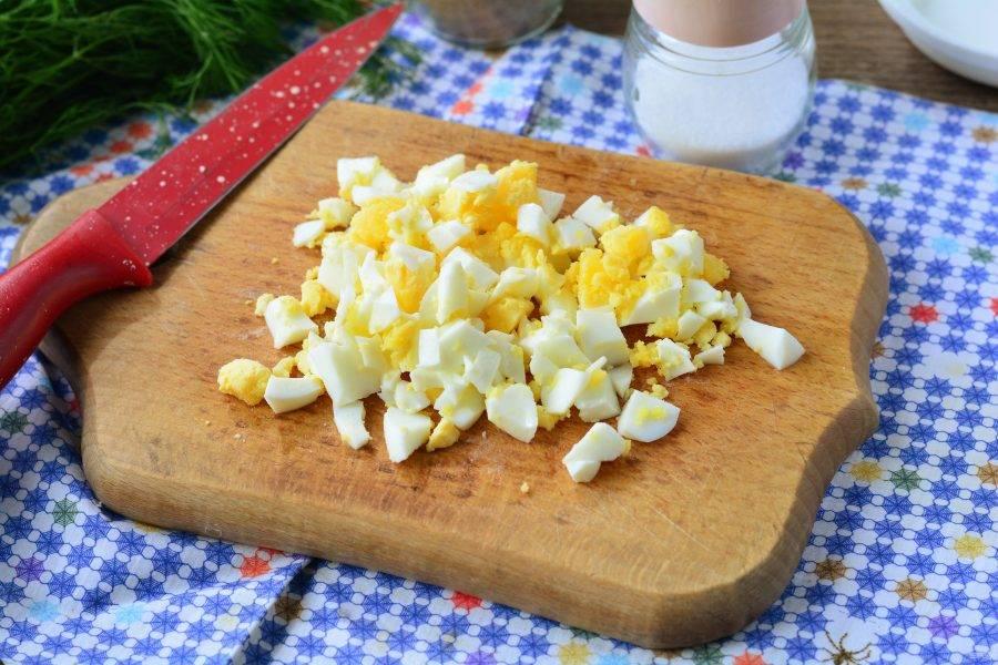 Сварите куриные яйца вкрутую, затем остудите, почистите и нарежьте кубиками.