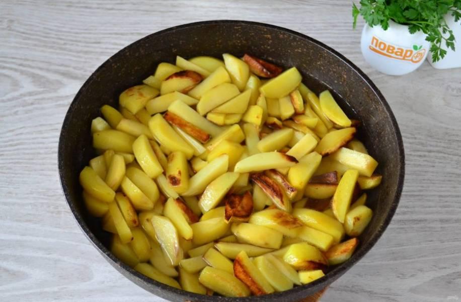 В сковороде разогрейте растительное масло, выложите картофель и обжарьте на среднем огне до образования золотистой корочки.