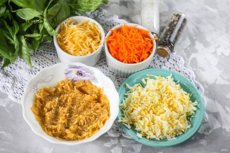 Очистите отварное куриное яйцо от скорлупы, промойте в воде. Натрите на терке с мелкими ячейками. Очистите морковь и яблоко от кожуры, промойте и так же натрите. Измельчите твердый сыр. Сбрызните лимонным соком яблочную нарезку.