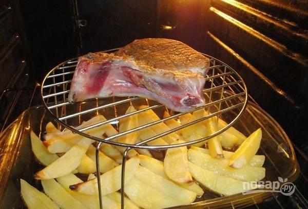 Картофель очистите, промойте, нашинкуйте крупной соломкой и посолите. Отправьте её в заранее разогретую до 200 градусов духовку на нижнюю полку, а сверху установите мясо. Запекайте 15 минут.