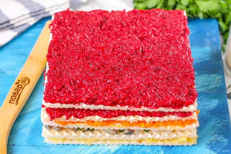 Обмажьте свекольной массой вафельный корж. Если массы много, то обмажьте два коржа. Можно сделать высокий закусочный торт, чередуя слои.