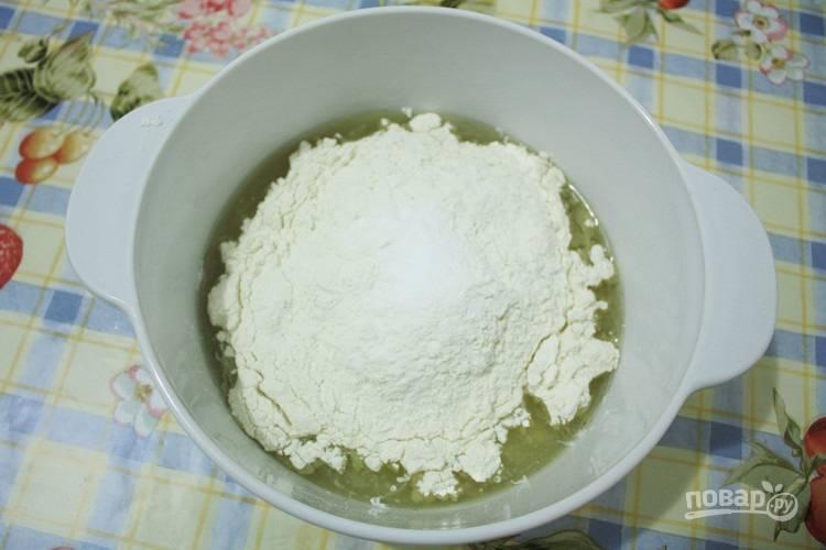 В большую миску влейте рассол. Растворите в нём сахар. Затем добавьте масло и просейте туда всю муку с содой.