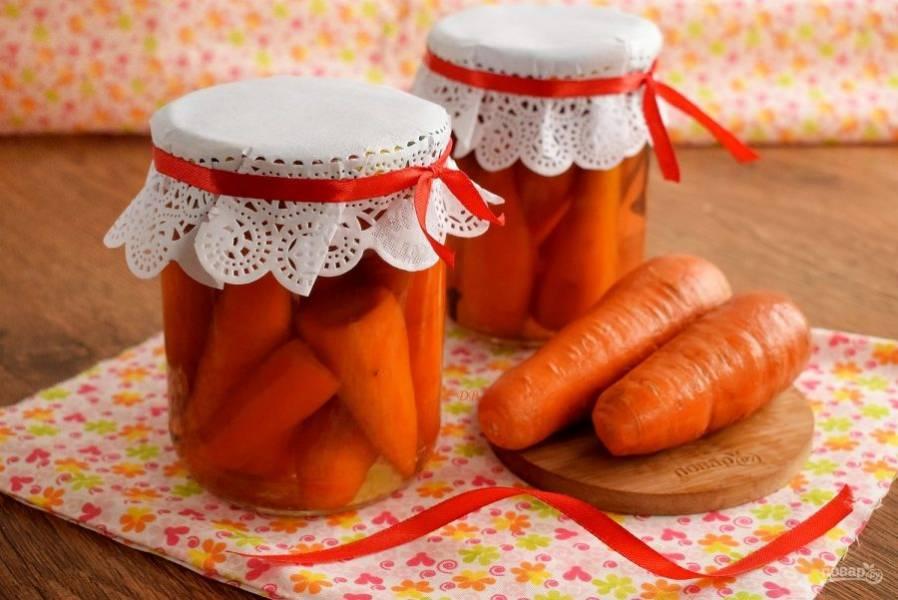 Разложите бланшированную морковь по стерилизованным банкам (0,5 л.), залейте горячим рассолом, прикройте крышками. Поставьте банки в кастрюлю с плотной тканью на дне. Залейте горячей водой по плечики банок, доведите до кипения и простерилизуйте в течение 40 минут. Закатайте крышки, укутайте банки, оставьте до полного остывания. Храните заготовку в прохладном месте.