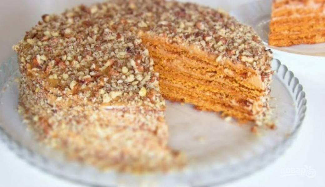 8. Промажьте кремом каждый корж, верх и бока. Верх и бока торта также посыпьте измельченной крошкой из обрезков и грецкими орехами. Теперь осталось дождаться, пока тортик пропитается.