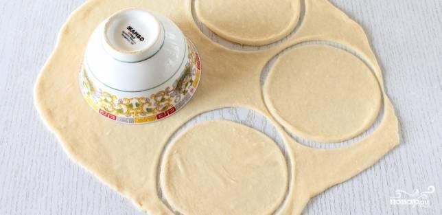 2. Готовое дрожжевое тесто разделите на несколько пластов. Раскатайте каждый пласт и вырежьте из них кружки по 10 см в диаметре.