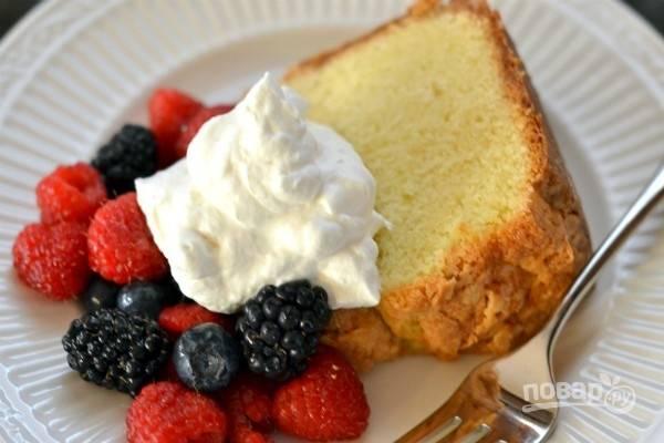 Подайте порционные кусочки сметанного коржа со свежими ягодами и взбитыми сливками.