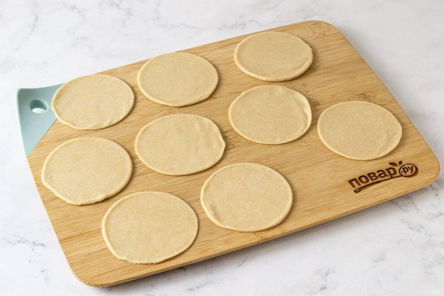 Раскатайте тесто толщиной 3-4 мм. Вырежьте кружки стаканом.