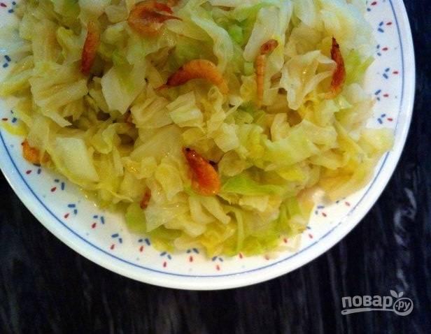 4.Добавьте к капусте креветки и перемешайте, подавайте блюдо сразу после приготовления.