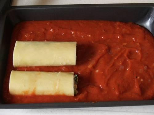 3. На дно жаропрочной формы выложить половину соуса. Каннеллони заполнить начинкой и выложить в форму.