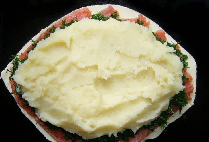 1. Обычно для такого пирога я беру уже готовое слоеное тесто. 500гр будет вполне достаточно. Раскатываем пласт и вырезаем из него форму рыбы. Сверху выкладываем картофельное пюре (толчем без добавления молока или воды) и нарезанную красную рыбу. Отлично сочетается с картофелем лосось и семга.
