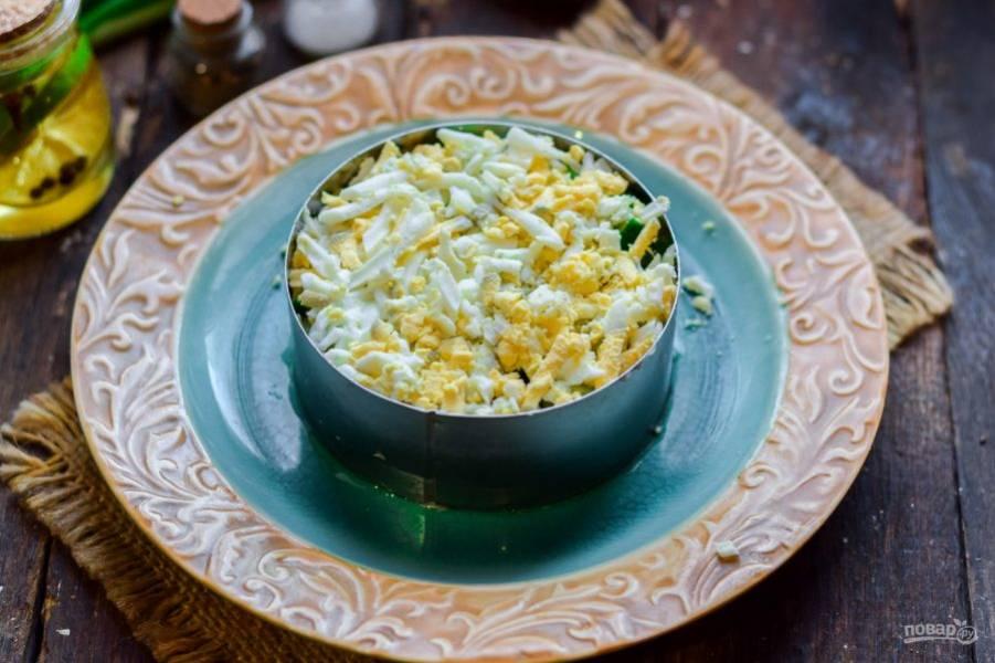 Куриные яйца отварите вкрутую, после яйца почистите от скорлупы, натрите на средней терке и переложите в салат. Смажьте слой майонезом.