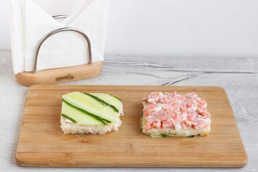 Один из тостов положите огурцом вниз, смажьте рыбной начинкой и сверху накройте вторым тостом.