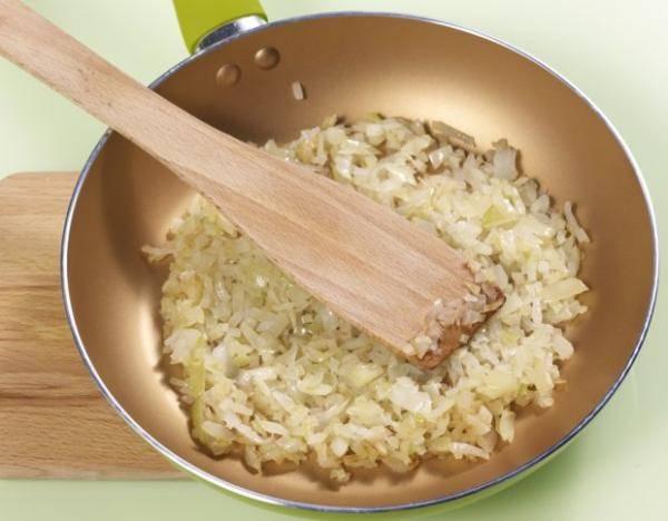 Лук репчатый мелко нарезаем и обжариваем на сковороде в оливковом масле.