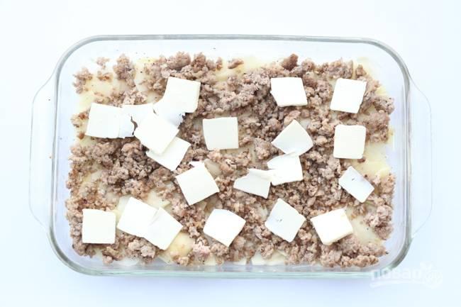 4.Поверх картошки выложите мясной фарш. Масло заранее отправьте в морозильник, затем нарежьте его небольшими кусочками и распределите сверху.