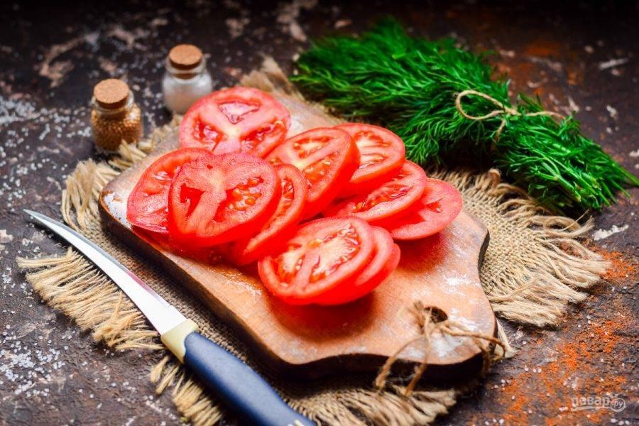 Помидоры вымойте и просушите, удалите место роста плодоножки. Нарежьте помидоры пластинами.