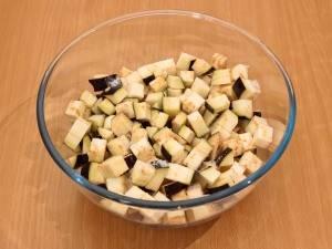 2. Нарежьте баклажаны кубиками и оставьте в миске, чтобы ушла горечь (предварительно их немного посолите).