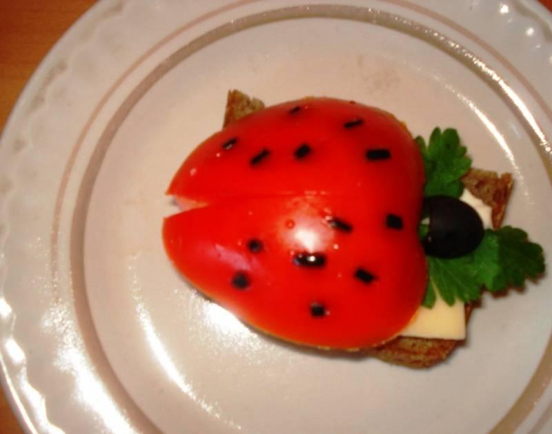 Положите на сыр листик зелени. Из половинки небольшого помидора и половинки маслины выложите божью коровку. Черные крапинки сделайте из мелких кусочков маслины. Бутерброды готовы к подаче на стол. Приятного аппетита и отличного настроения!