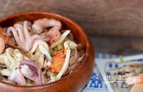 Откройте коктейль из морепродуктов и переложите его в блюдо. Можете добавить немного пряного масла, в котором был коктейль, но не перестарайтесь, чтобы салат не получился слишком жирным и тяжелым.