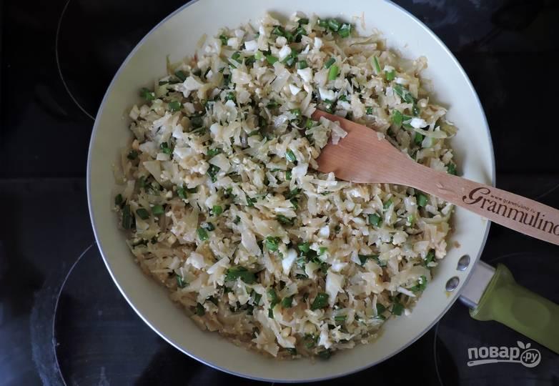 3. Тем временем как раз удобно сделать начинку. Мелко шинкуем лук и капусту, добавим отваренные и измельченные яйца. На сливочном масле томим капусту вместе со специями, чтобы она стала мягкой. Дальше смешаем все ингредиенты и еще пару минут потомим.