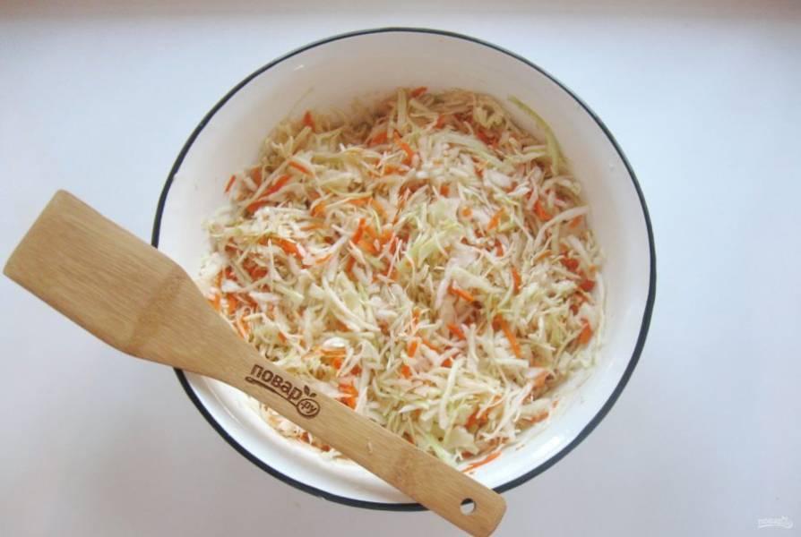 Перемешайте морковь с капустой и солью. Тщательно пожмите руками.