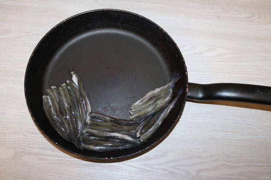 В большую сковороду с высокими бортиками брюшками вниз выкладывайте плотно друг к другу мойву.