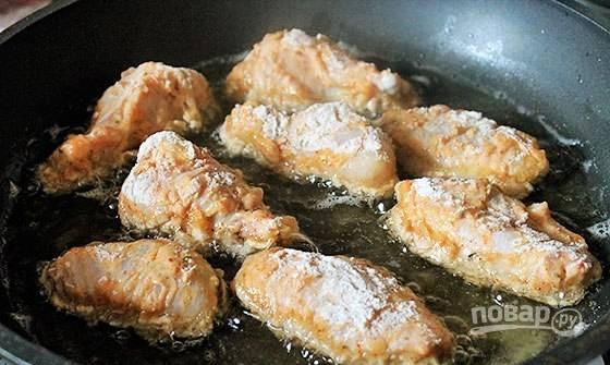 Разогрейте масло в глубокой сковороде. Обжарьте в нём куриные крылья в течение 15-20 минут, не забывая их переворачивать.