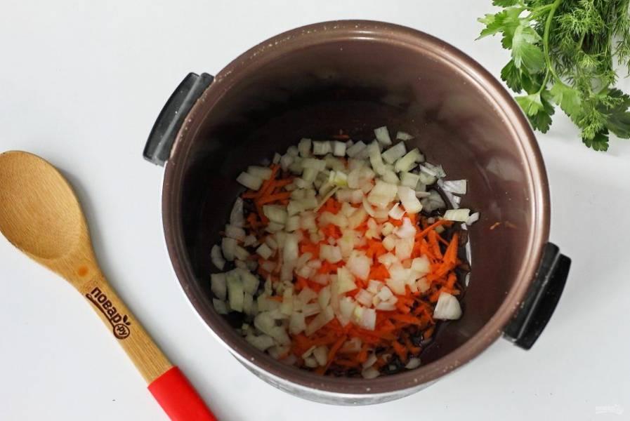 Чашу мультиварки ополосните, налейте масло, выложите нарезанный кубиками лук и тертую морковь.