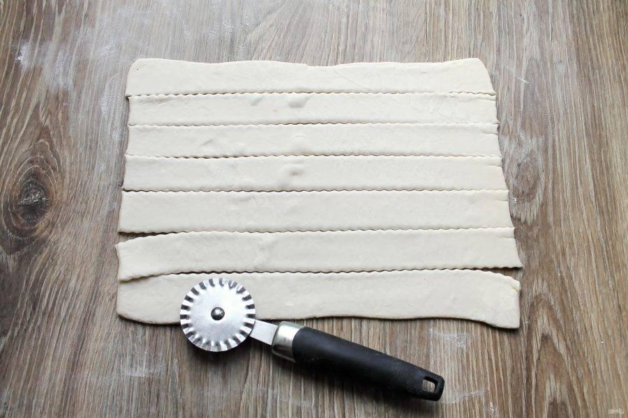 Рабочую поверхность посыпьте мукой. Немного раскатайте тесто в одном направлении в прямоугольник. Разрежьте его вдоль на полоски  шириной 2-2,5 сантиметра.