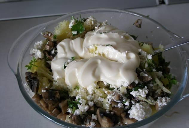 Соединяем в тарелке: тертый картофель, измельченную зелень, грибы с луком, майонез и творожный сыр. Добавляем по вкусу соль и перец, перемешиваем до однородности.