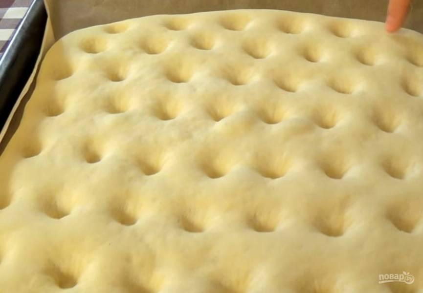 4.  Посыпьте доску мукой, распластайте тесто по форме противня, накройте полотенцем и оставьте на 30 минут при комнатной температуре. По всей лепешке сделайте углубления пальцем и смажьте смесью оливкового масла с водой.