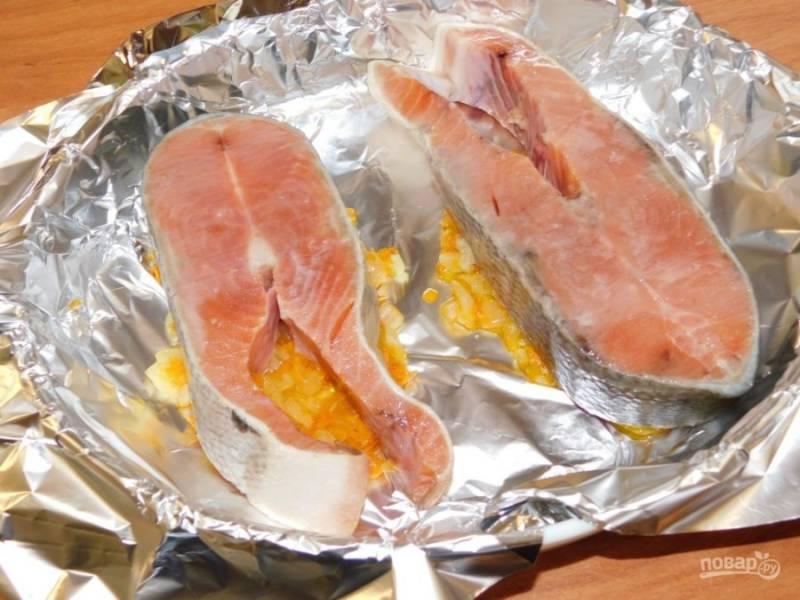 Выложите овощи в форму для запекания, застеленную фольгой. Сверху выложите рыбные стейки, сбрызните лимонным соком и посолите немного.