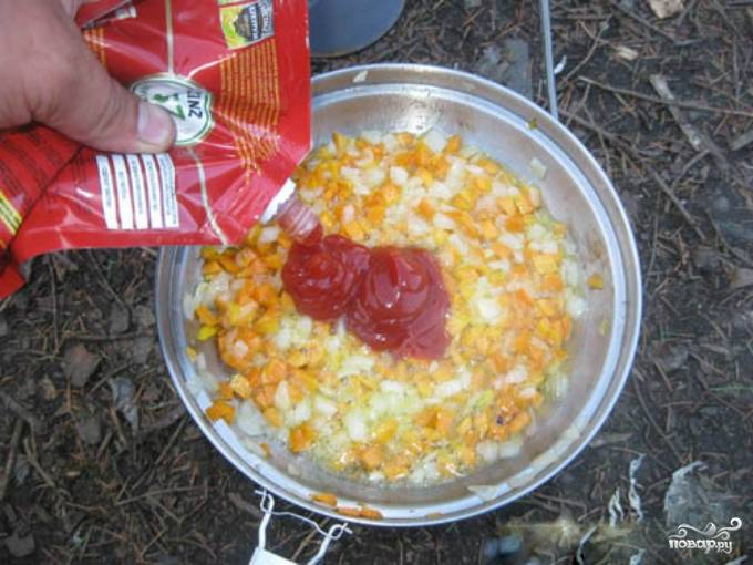 4. Репчатый лук необходимо очистить от шелухи и порезать небольшими кубиками. Морковь также промойте, очистите и потрите на крупной терке, либо порежьте мелкими кубиками. На разогретую сковороду с растительным маслом добавьте лук и морковь. Обжаривайте 5 минут на среднем огне, постоянно помешивая. Добавьте кетчуп, все хорошо перемешайте.