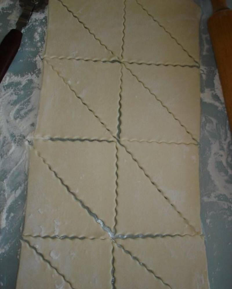 Для начинки, обжариваем измельченные грибы с луком, добавив зелень и сметану. Слоеное тесто раскатать и нарезать прямоугольниками, а затем треугольниками.