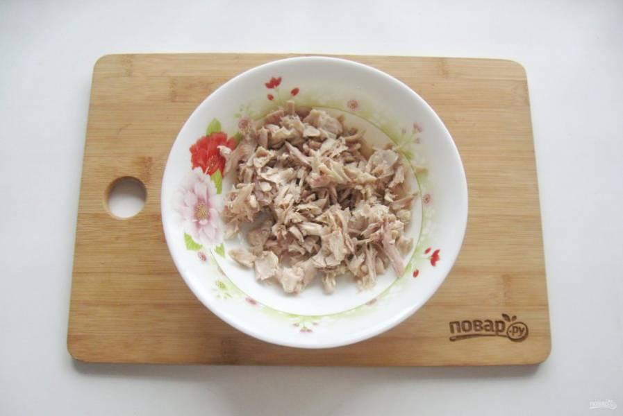 Нарежьте отварную курицу и выложите в салатник.