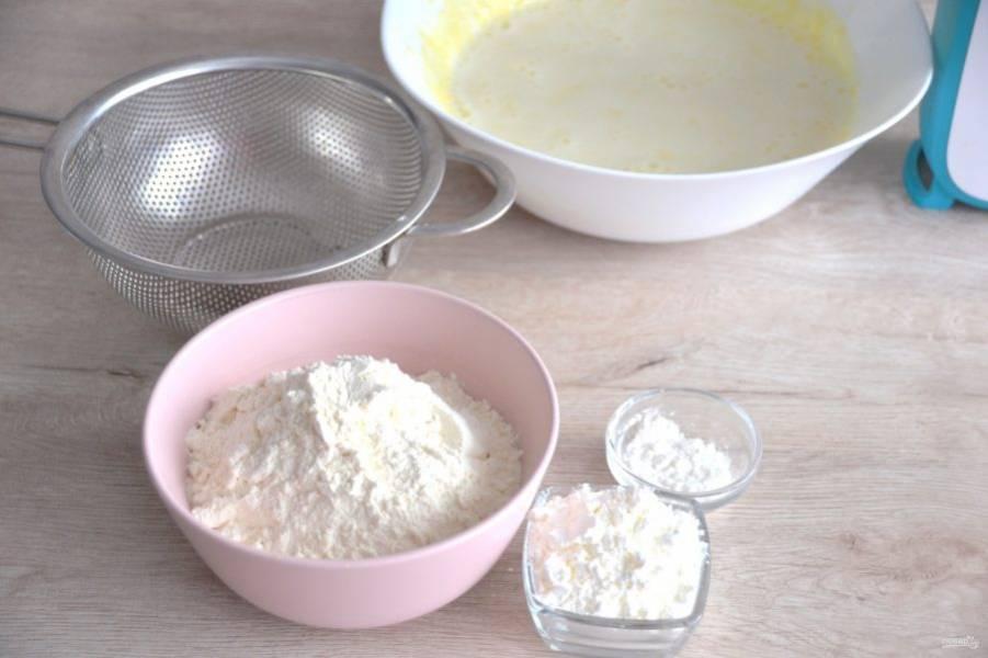 Смешайте муку, разрыхлитель и крахмал. Всыпьте в молочно-желтковую смесь частями, замесите тесто.