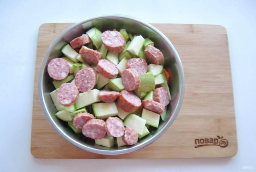 Любые копченые колбаски по вашему вкусу нарежьте и добавьте к овощам.