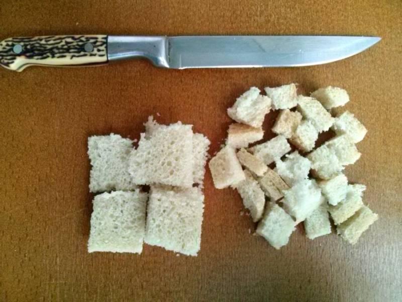 Возьмите ломтики черствого хлеба, обрежьте с них корочки. Корочки и часть хлеба порежьте на кубики, а после обжарьте на протяжении нескольких минут на сухой горячей сковороде.