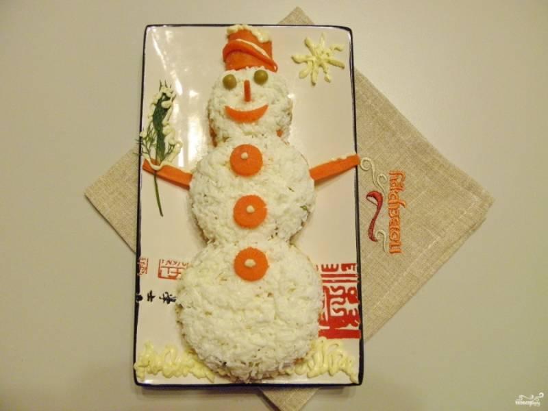 И последние штрихи: оформите рот, нос, глаза, сделайте ведерко-шапочку, руки. Майонезом оформите снежинку, снег на ведерке, на руках и под снеговиком. Вот и всё, салат готов!