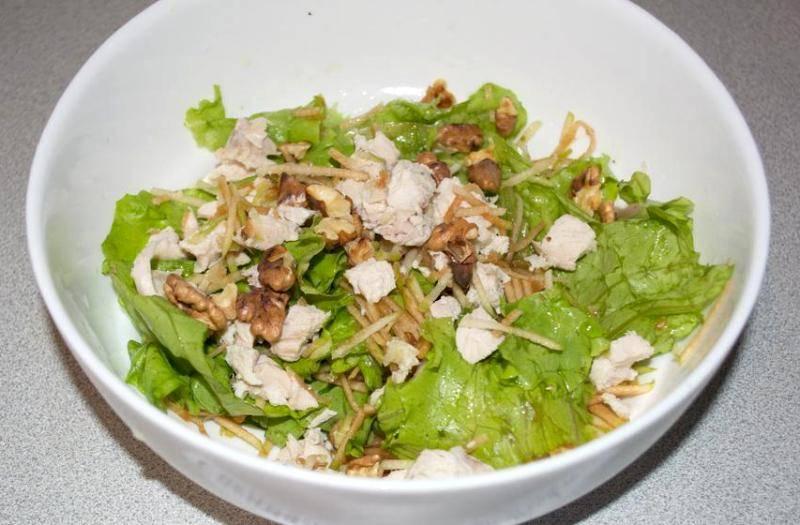 Теперь заправляем салатные листья растительным маслом, сверху выкладываем нарезанное на кусочки мясо курицы, орехи и яблоко, посыпаем салат солью и перцем.