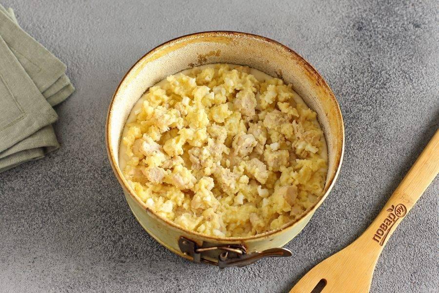 Форму для запекания смажьте маслом. Дно и бока обсыпьте мукой или манкой (размер моей формы 18 см. в диаметре). Налейте половину порции теста и сверху равномерно распределите всю начинку.