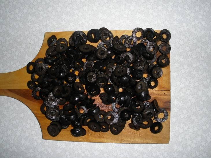 Режем маслины напополам, достаем из них косточки, если есть.