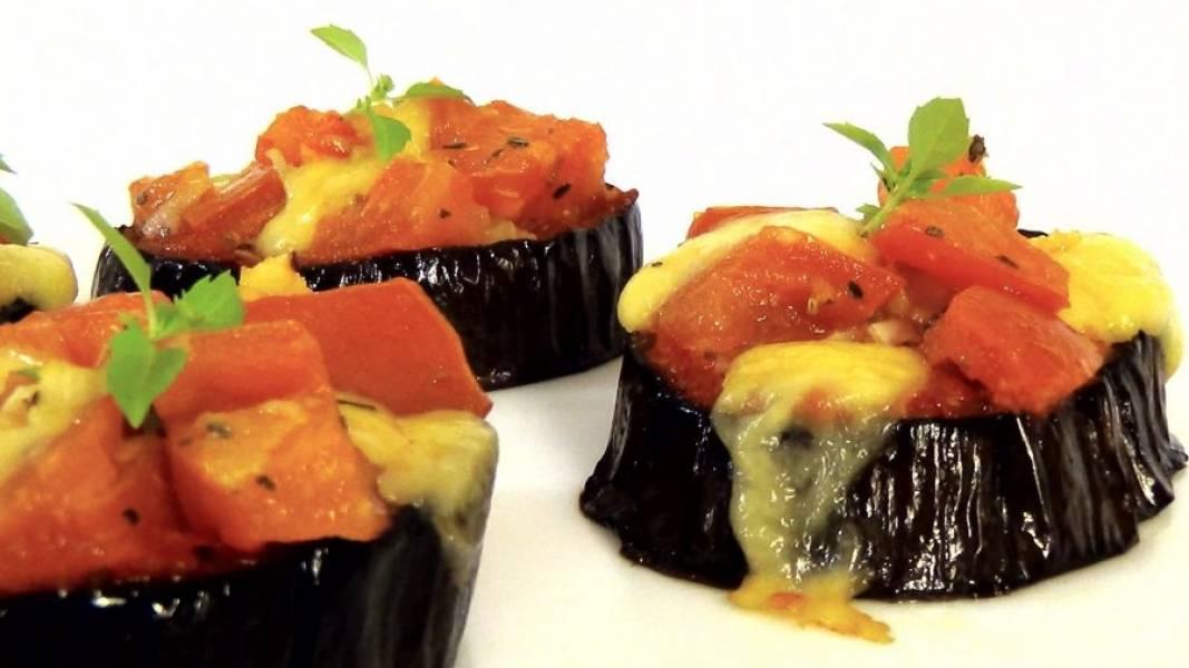 4. Выложите начинку на баклажаны и отправьте в разогретую до 220 градусов духовку на 10 минут. Украсьте листьями базилика. Приятного аппетита!