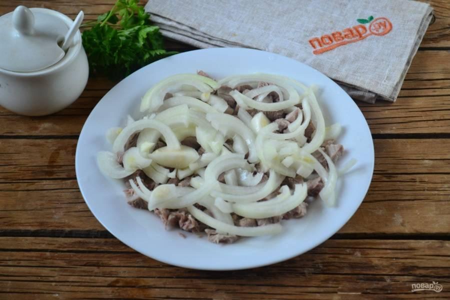 Начинайте собирать салат. На дно плоской тарелки положите мясо, сверху выложите лук, предварительно отжатый от маринада.