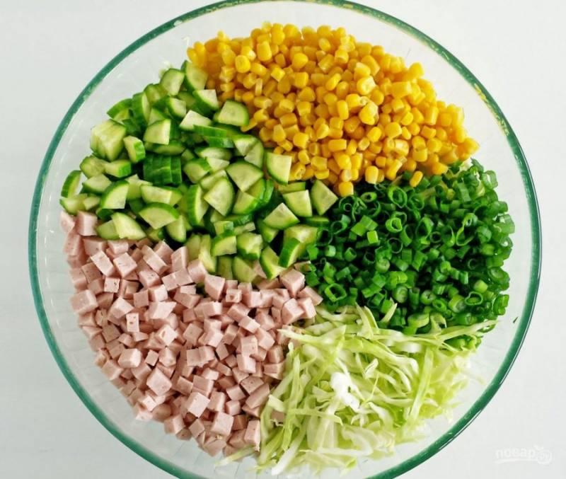 1.Мою огурцы, зелень и капусту. Огурцы нарезаю мелкими кусочками, капусту шинкую мелко, зелень измельчаю ножом. Ветчину нарезаю небольшим кубиком. Сливаю воду с консервированной кукурузы. Выкладываю все измельченные ингредиенты в миску.